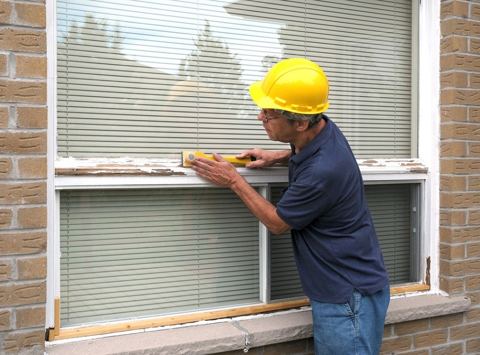 Workman repairing a large picture window; Shutterstock ID 16627522; PO: Zeus