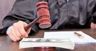 Midsection of judge hitting mallet on banknotes at desk